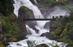 Bridge across the stream near a powerful waterfall. Surrounded by misty clouds Royalty Free Stock Image