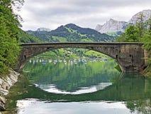 Bridge across the stream Schrabach Schraehbach and on alpine Lake Wagitalersee Waegitalersee, Innerthal. Canton of Schwyz, Switzerland royalty free stock photo