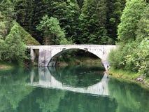 Bridge across the stream Schrabach Schraehbach and on alpine Lake Wagitalersee Waegitalersee, Innerthal. Canton of Schwyz, Switzerland royalty free stock photography