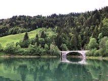 Bridge across the stream Schrabach Schraehbach and on alpine Lake Wagitalersee Waegitalersee, Innerthal. Canton of Schwyz, Switzerland stock image