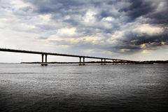 Bridge across the wide river and storm clouds. Royalty Free Stock Photo
