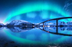 Bridge and aurora borealis over snowy mountains. Lofoten islands, Norway. Amazing northern lights and reflection in water. Winter landscape with starry sky stock photos