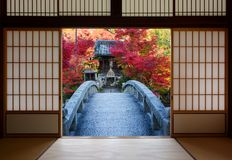 Bridge and autumn trees seen through the open doors of an old Japanese dojo. Sliding rice paper doors on an ancient Japanese dojo and a stone bridge leading to Stock Photography