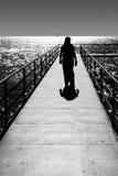 Bridge backlighting. Female walking along a bridge Royalty Free Stock Images