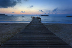 Bridge on beach in sunset Stock Image