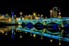 Bridge in Belfast. A bridge in Belfast reflecting in a river at night stock photography