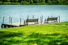 Bridge with benches stood on river. Stock Image