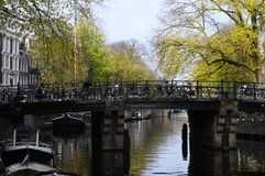 Bridge and bikes on canal in Amsterdam Stock Photography