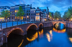 Bridge Blue hour arch over canal. In Amsterdam Netherlands. Famous landmark old town evening traditional Dutch architecture Royalty Free Stock Photo
