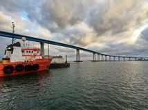 Bridge with boat in foreground under stormy clouds Royalty Free Stock Photos