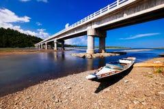 Bridge. Boat under the bridge. When river meets the sea Royalty Free Stock Photo
