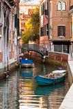 Bridge and boats in Venice. Bridge over a Venetian Canal and boats. Reflections are on the water Stock Photos