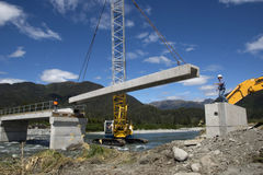 Bridge builders. Builders construct a concrete bridge over a small river in Westland, New Zealand Royalty Free Stock Photography