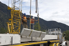 Bridge builders. Builders unload modules for a concrete bridge over a small river in Westland, New Zealand Royalty Free Stock Image