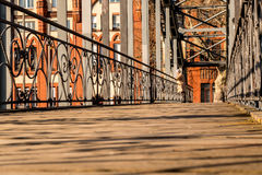 Bridge with building in background. A wooden bridge in the city on a sunny day Stock Images