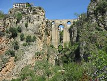 Bridge and building on the cliff edge at Ronda, Andalucia, Spain. Arched bridge across the gorge at Ronda with buildings visible through the arches and a stock photography
