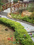 Bridge in Chinese park. Scenic view of paved pathway and bridge in traditional Chinese garden Royalty Free Stock Photo
