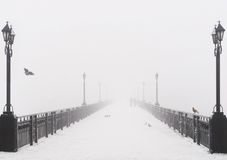 Bridge city landscape in foggy snowy winter day Stock Photo