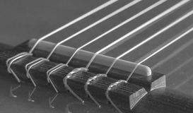 Close-up of the bridge of a classical acoustic guitar. The bridge of a classical acoustic guitar with its strings. Grayscale image, ideal for backgrounds.nThe Stock Image
