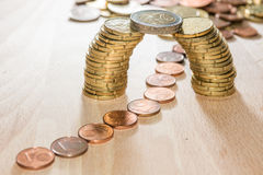 Bridge of coins. Bridge build out of euro coins with cents flowing underneath it Royalty Free Stock Photo