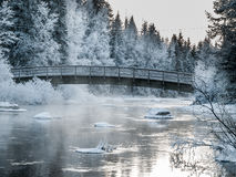 Bridge over river with ice flows. Curved bridge with railings across river in extreme Winter weather with ice blocks in the waters and snow  dusted  fir trees Stock Image