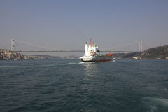 Bridge connecting Europe and Asia in Turkey. Merchant ship sailing to the bridge over Bosphorus connecting european and asian part of Istanbul Stock Photo