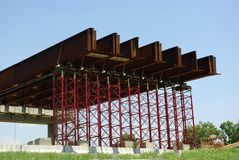 Bridge Construction. During construction of a bridge, steel I-beams are held in place by temporary support structures.  This is the beginning stages of a Stock Photo