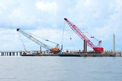 Bridge construction with crawler cranes on flat boats floating on water Royalty Free Stock Image