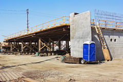 Bridge Construction with Porta Potty. Bridge construction begins to go over a road and while a porta potty is good to have on site Royalty Free Stock Photo