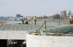 Bridge Construction Workers. Workers actively working on top of new bridge construction site.  Green rebar rods are the underlying supports for poured cement Stock Photography