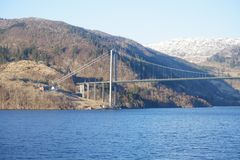 Bridge cross the lakes, Norway. Bridge cross the lake, Norway. It is winter and a lot of snow on the mountain. It is blue water in the lake royalty free stock photography
