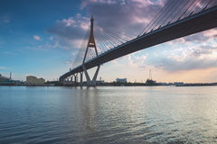 The bridge crosses the river with clouds sky and rays of sunset Royalty Free Stock Photo