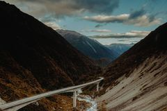 Bridge crossing river in valley with mountains royalty free stock photos