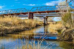 Bridge crossing a small river with blue sky background Stock Photos
