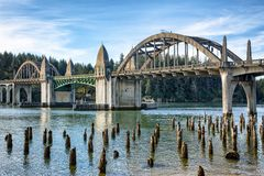 Bridge crossings and river with tree stumps, Florence OR. Siuslaw River Bridge from the Florence Marin withold wooden piles on foreground, Oregon USA Royalty Free Stock Photo