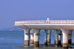 Bridge curve at sea coast. A white bridge curve under blue sky,extending at sea coast on the sea water, shown as different feature of road or bridge construction Stock Image