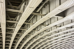 Bridge With Curved Girders. The underside of a bridge in London shows the architectural details of a geometric pattern of curved beams and girders that provide Royalty Free Stock Photography