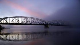 Bridge disappearing in fog. A sunrise on the bridge disappearing in the dense fog Stock Photography