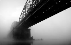 Bridge disappearing in fog. A bridge disappearing in the dense fog. B&W picture royalty free stock image