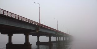Bridge disappearing in the fog. The New bridge with red railing over the Dnepr river disappearing in the fog Stock Image