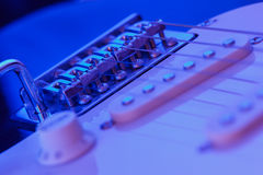 Bridge of an electric guitar with blue light Stock Image