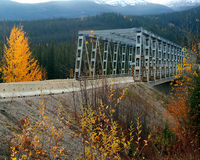 Bridge With Fall Colors. Steel bridge on a mountain road in Canada surrounded by fall colors with snow capped peaks behind Stock Photo