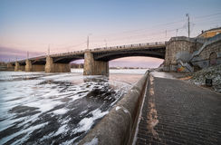 Bridge in fetters of ice. Warm colors of cold evening above the the bridge over the frozen river Stock Photos