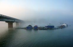 Bridge, fishing hamlet on lake in fog Royalty Free Stock Images