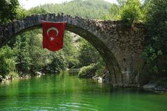 Bridge flag banner red color green water travel turkeytime Turkey nature trees. Day no people outdoors in the Turkey travel summer sunlight water green color royalty free stock photography