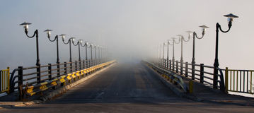 Bridge into the fog Stock Images