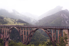 Bridge in foggy mountains Stock Photos