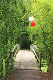 Bridge in the forest decorated with balloons for celebrations, weddings and Mothers Day. Idyllic bridge in the forest with two balloons for celebrations stock images