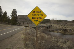 Bridge freezes before road sign next to river Royalty Free Stock Image