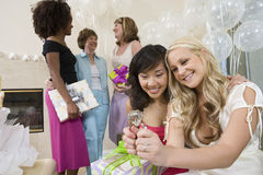Bridge And Friend Looking At Engagement Ring At Hen Party. Happy bridge and friend looking at engagement ring with people standing in the background Royalty Free Stock Image